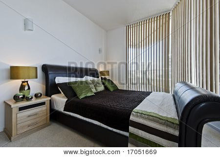 luxury modern bedroom with a leather coated bed frame bedside tables and decoration