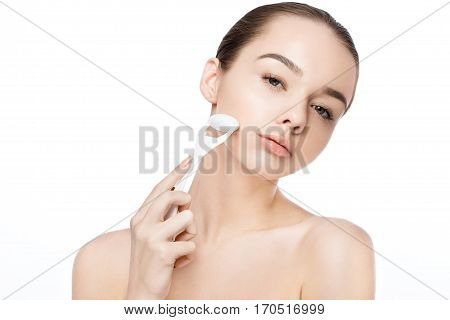 Beautiful girl holding drainage massage face roller on white background