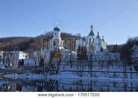 Churches of Sviatohirsk Lavra. Sunny day in January. On the waterfront
