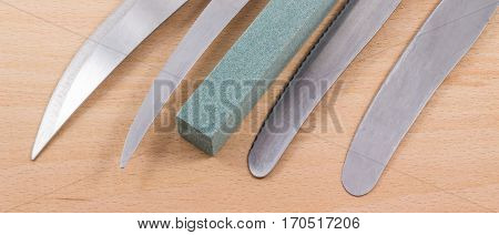 grindstone and blade kitchen knives on a wooden background, what we use every day in the kitchen