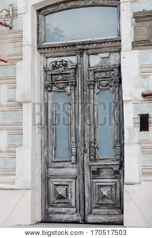Old grey vintage double-leaf door made of carved decorations painted in white wood framed with biege stones in Rostov-on-Don Russia