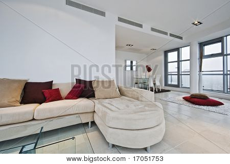 massive penthouse living room  with L shaped sofa and dining area