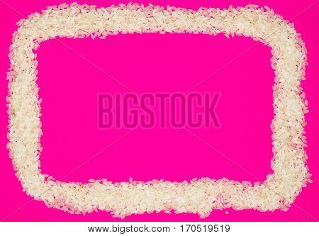 Basmati white uncooked rice on hot pink background. minimalism background isolated