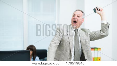 Angry business man throwing away his smartphone