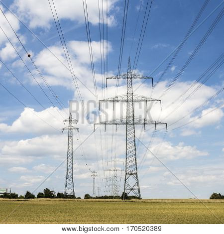 Electric Pylon On  Field Under Blue Sky