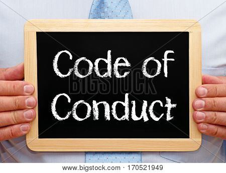 Code of Conduct - Businessman holding chalkboard with text