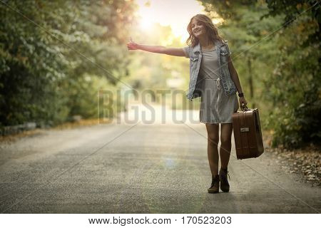 Beautiful young woman with suitcase hitchhiking on road