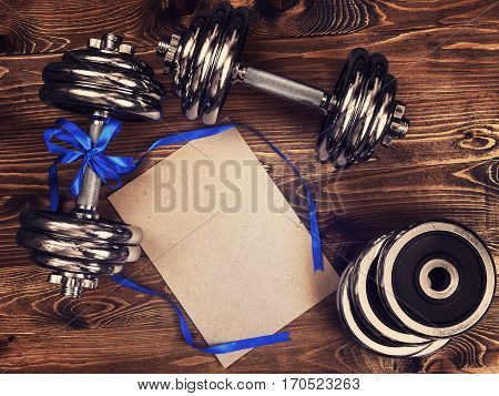 Toned image of metal dumbbells, blue atlas ribbon and a sheet of craft paper