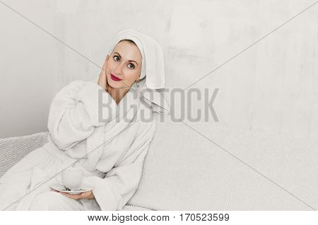 Beautiful girl sitting on the sofa in a fluffy Bathrobe in a room with no Wallpaper on the walls needed to be repaired. White background, high key, place for text.