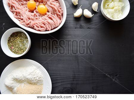 Raw minced meat with seasonings on dark background. minced meat and ingredients on the table. horizontal view from above
