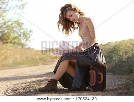 Beautiful young girl with map sitting on suitcase