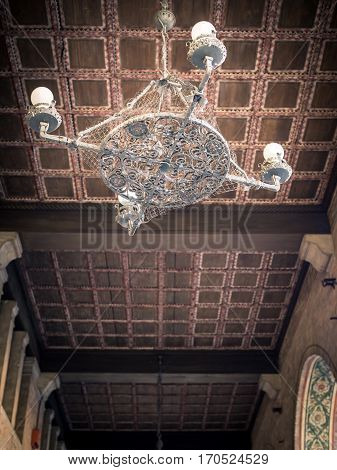 Wrought iron chandelier and coffered wooden ceiling.