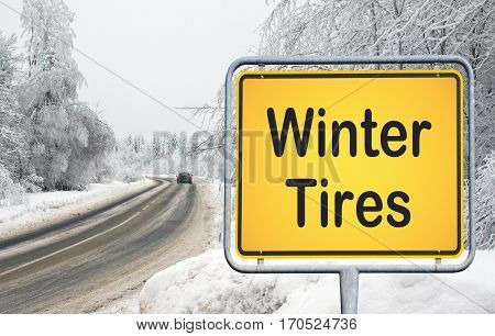 Winter Tires - traffic sign with text and road in the forest