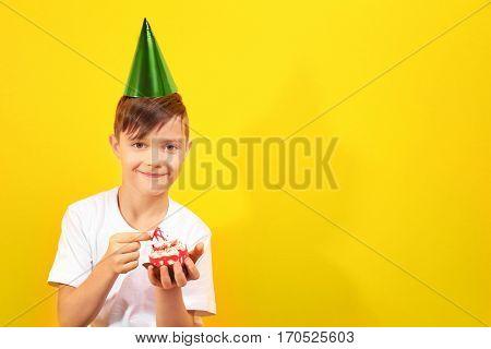 Cute boy  with birthday mini cake on yellow background