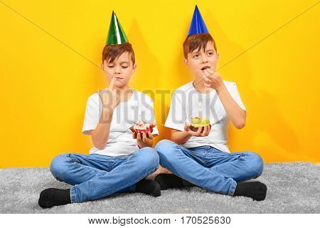 Cute boys with birthday mini cakes on yellow background