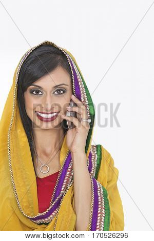 Portrait of Indian woman in traditional wear attending phone call over gray background