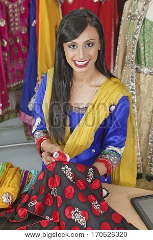 Portrait of an Indian female dressmaker matching thread color with the cloth