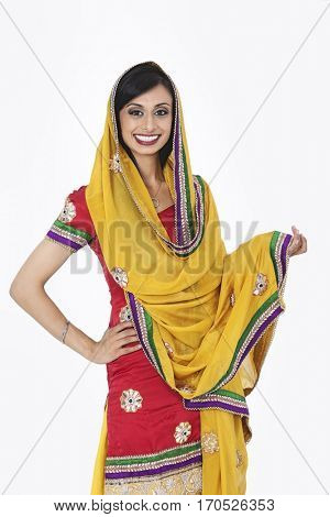 Portrait of an attractive Indian female in traditional wear standing over gray background