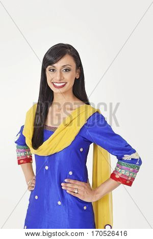 Portrait of beautiful Indian woman in traditional wear standing with hands on hips over gray background