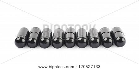Pile of softgel black capsule pills isolated over the white background