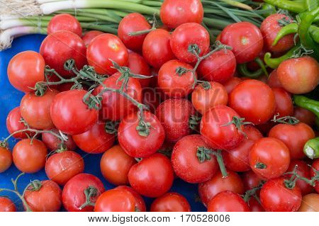 Natural tomatoes with small green onions and peppers