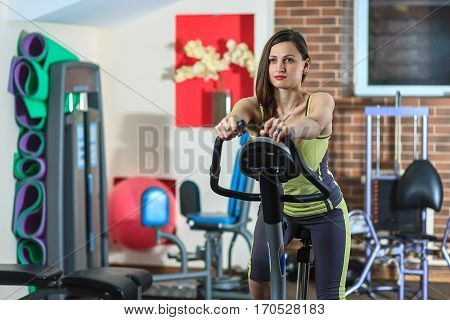 Young Beautiful White Girl In A Yellow And Gray Sports Suit Is Engaged On A Stationary Bike In The F