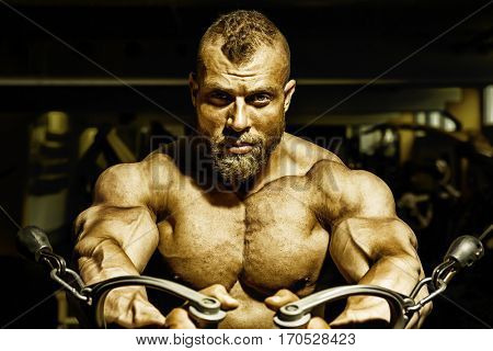 An image of a handsome bearded bodybuilding man doing chest workout