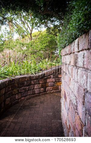 Old brick walls following curved path with overhanging trees