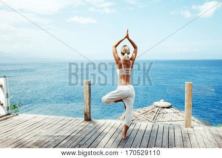 Young woman doing yoga asana in the nature with the ocean view. Morning workout outdoors, sports and healthy lifestyle.
