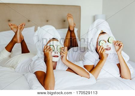 Mom and her 10 years old preteen daughter chilling in the bedroom and making clay facial mask. Mother with child doing beauty treatment together. Morning skin care routine.