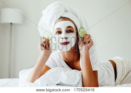 10 years old preteen chilling in the bedroom and making clay facial mask. Teenage girl doing anti blemish skin treatment. Morning skin care routine.