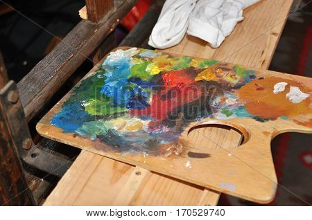 Artistic painter's wooden palette wit colors in atelier