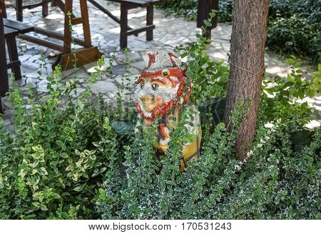 Gnome Effigy Of Gypsum In The Bushes. Park Figurines