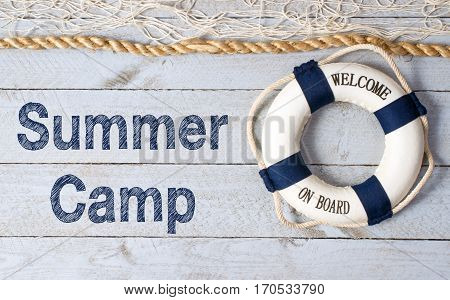 Summer Camp - lifebuoy with text on wooden background