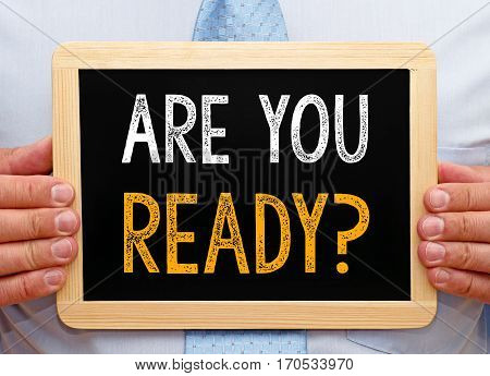 Are you ready - Businessman holding chalkboard with text