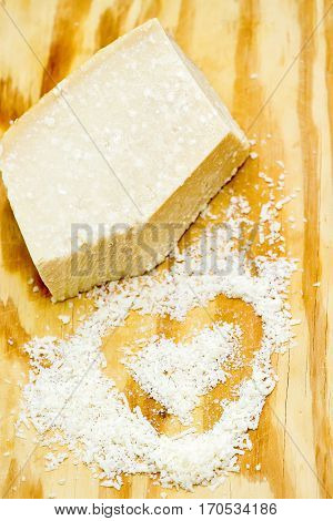 Pieces of parmigiano reggiano or parmesan cheese on wood board. Parmesan is hard cheese uses in pasta dishes soups risottos and grated over salads. Top down of single tasty fresh yellow big segment piece of parm and finely grated cheese.