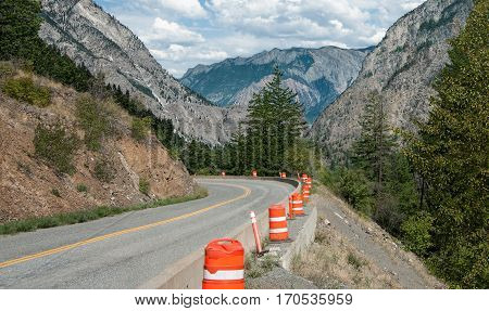 Mountain Road Repairs:  Orange barrels mark the edge of a road under repair in the mountains of British Columbia.