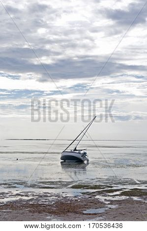 A sailboat stranded in shallow water on an overcast day. Crystal Beach, Florida.