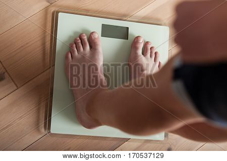 Young Teenager Weighing Himself On A Scale