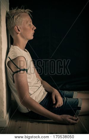 Teenage drug addict shooting up with heroin sitting slumped against a wall with a cuff on his arm from injecting the narcotic into his vein poster