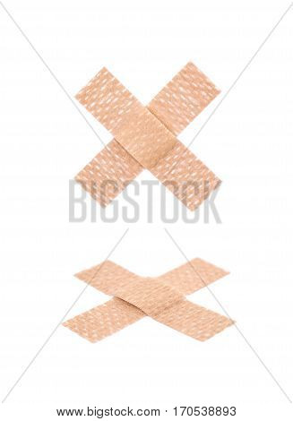 Cross shaped adhesive bandage sticking plaster isolated over the white background, set of two different foreshortenings