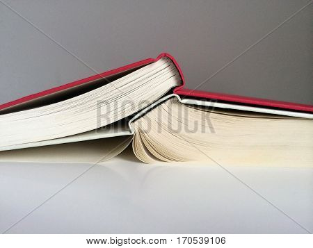 red and white book sprawled upon a desk