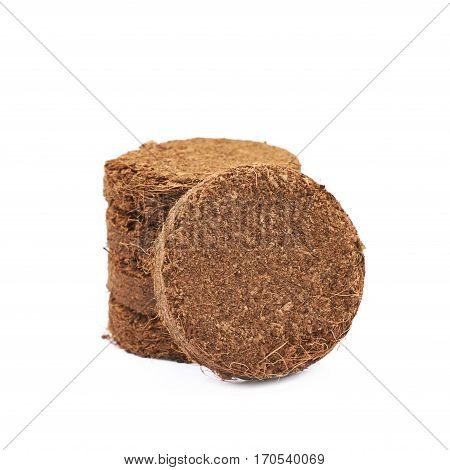 Pile of multiple compressed compost tablets, composition isolated over the white background
