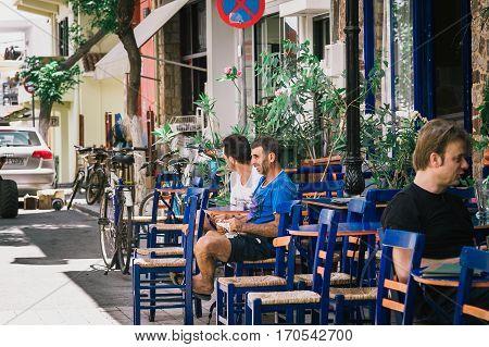 PALEOCHORA, CRETE, GREECE - JUNE 2016: Men are sitting at traditional Greek tavern at Paleochora town on Crete island