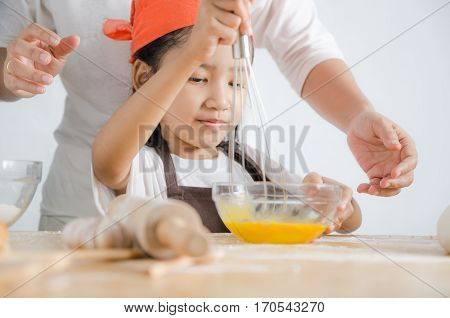 Asian little girl using stainless steel whisk to mix the egg for making bakery with mom
