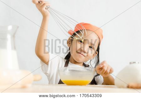 Asian little girl using stainless steel whisk to mix the egg for making bakery