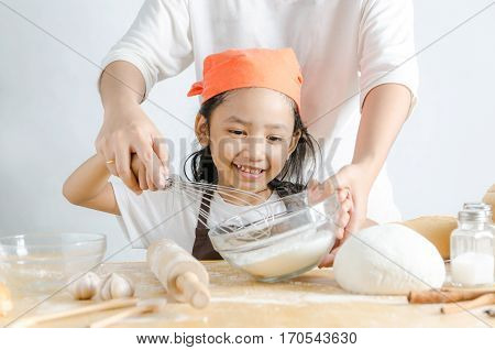 Close up shot Asian little girl holding stainless steel whisk and bakery dough flour in glass bowl and mother hands shallow depth of field