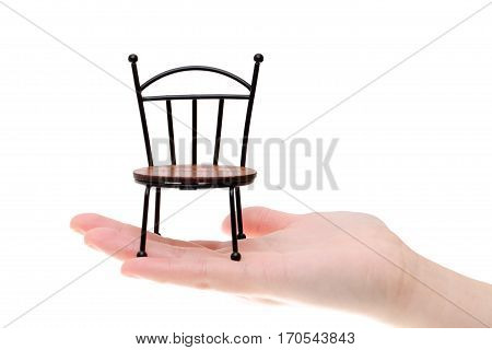 small toy chair on the hand isolated on white background