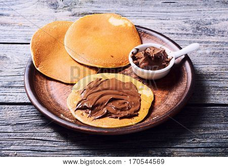 breakfast . Pancakes with chocolate spread nutella .