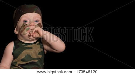A Child Soldier In Uniform With War Paint On His Face. Boy In Uniform Against The Background Of Camo